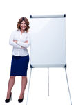 Businesswoman standing near blank flipchart Stock Images