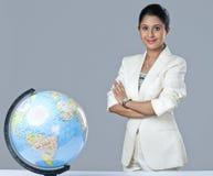 Businesswoman standing near globe. Businesswoman standing near a globe and smiling Royalty Free Stock Image