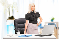 Businesswoman standing next to desk with laptop Stock Photo