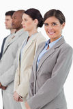 Businesswoman standing next to her associates. Smiling businesswoman standing next to her associates against a white background Stock Photo