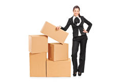 Businesswoman standing next to a pile of boxes Royalty Free Stock Photos