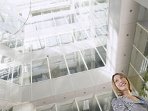 Businesswoman Standing In Office Atrium. Low angle view of a smiling businesswoman standing in atrium of office building Royalty Free Stock Photos