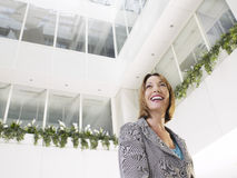 Businesswoman Standing In Office Atrium. Smiling businesswoman standing in atrium of office building low angle view Stock Image