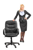 Businesswoman standing by an office chair Stock Image