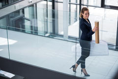 Businesswoman standing at office corridor with chart holder Stock Image