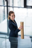 Businesswoman standing at office corridor with chart holder Royalty Free Stock Photos