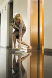 Businesswoman standing beside office elevator, picking up folder from floor, surface level Royalty Free Stock Image