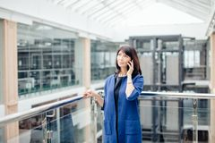 Excited Senior Business Lady Talking on Phone. Businesswoman standing in office lobby, on mobile phone call, taking out personal organizer Royalty Free Stock Image
