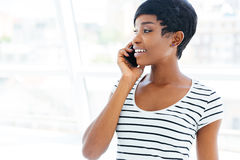 Businesswoman standing in office and talking on cell phone Stock Photo