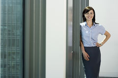 Businesswoman standing beside office window, hand on hip smiling, portrait Royalty Free Stock Photography