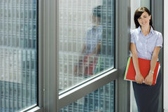 Businesswoman standing beside office window, holding red folder, smiling, portrait Royalty Free Stock Images