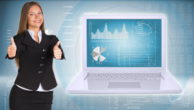 Businesswoman standing with open laptop. Businesswoman with open laptop. High-tech graphs at backdrop Stock Images