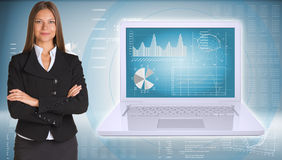 Businesswoman standing with open laptop. Businesswoman with open laptop. High-tech graphs at backdrop Stock Photography