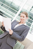 Businesswoman standing outdoors reading paperwork Stock Images