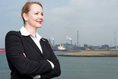 Businesswoman standing outside industrial harbor Stock Images