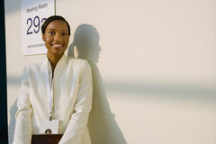 Businesswoman standing outside meeting room, casting shadow on wall, smiling, portrait Stock Photo
