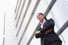 Businesswoman standing outside office building. Businesswoman standing outside modern office building Royalty Free Stock Photos
