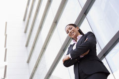 Businesswoman standing outside office building. Businesswoman standing outside modern office building Stock Images