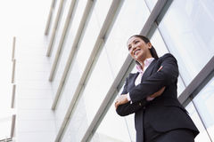 Businesswoman standing outside office building. Businesswoman standing outside modern office building Royalty Free Stock Photography