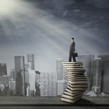 Businesswoman standing on a pile of books Royalty Free Stock Photography