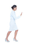 Businesswoman standing and pushing Stock Image