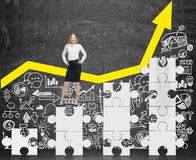 Businesswoman standing on puzzle pieces Stock Photo