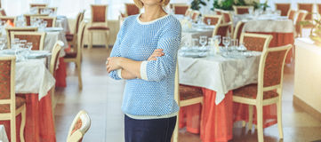 Businesswoman standing in a restaurant by day. Businesswoman standing in a restaurant Stock Photos