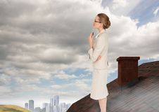 Businesswoman standing on Roof with chimney and city in distance Royalty Free Stock Photo