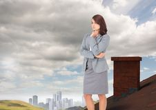 Businesswoman standing on Roof with chimney in country with city in distance Royalty Free Stock Image