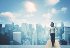 Looking at future city. Businesswoman standing on a roof and looking at future city Royalty Free Stock Photography