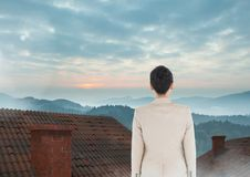 Businesswoman standing on Roofs with chimney and misty colorful landscape Royalty Free Stock Photo