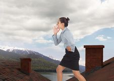Businesswoman standing on Roofs with chimney and mountain lake landscape Royalty Free Stock Image