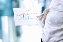 Businesswoman standing and showing graphic. Presentation. Royalty Free Stock Photo