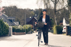 Businesswoman standing on the Street with bike stock photography