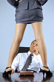 Businesswoman standing on table in front of businessman at office Royalty Free Stock Photography