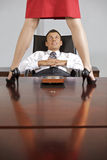 Businesswoman standing on table in front of businessman at office Stock Image