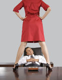 Businesswoman standing on table in front of businessman at office Royalty Free Stock Images