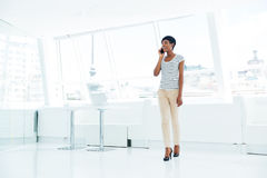 Businesswoman standing and talking on mobile phone in office Stock Photography