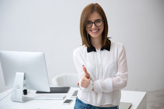 Businesswoman standing with thumb up Stock Image