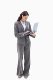 Businesswoman standing and typing on a laptop Stock Images