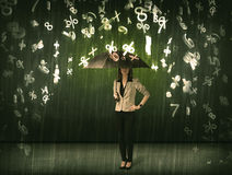 Businesswoman standing with umbrella and 3d numbers raining conc Stock Photos