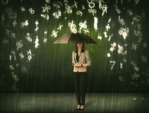 Businesswoman standing with umbrella and 3d numbers raining conc Stock Images