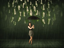 Businesswoman standing with umbrella in dollar bill rain concept Stock Photography