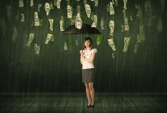 Businesswoman standing with umbrella in dollar bill rain concept Stock Photo