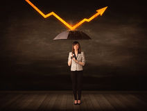 Businesswoman standing with umbrella keeping orange arrow Royalty Free Stock Image