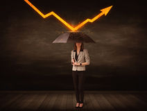 Businesswoman standing with umbrella keeping orange arrow Stock Photo