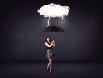 Businesswoman standing with umbrella and little storm cloud Royalty Free Stock Image