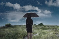 Businesswoman standing with an umbrella in rain Royalty Free Stock Images