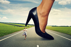 Businesswoman standing under big heel Stock Image