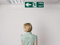 Businesswoman Standing Under Exit Sign Royalty Free Stock Image